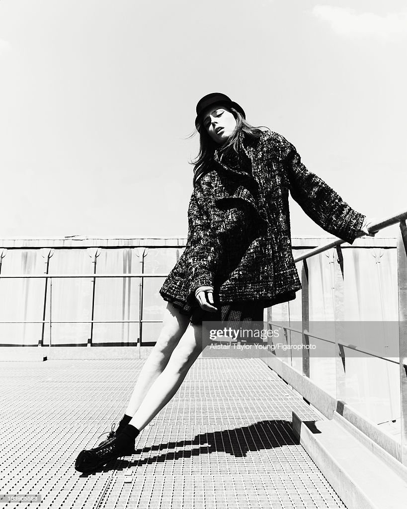 107230-019. Model Coco Rocha poses at a fashion shoot for Madame Figaro on July 19, 2013 in Paris, France. Coat, shirt and jewelry (Chanel), hat (Maison Michel), tights (Falke), shoes (Christian Louboutin).