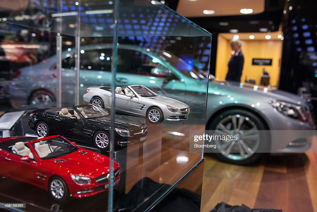 Model convertible cars sit in a display case beside a Mercedes-Benz S350 automobile, produced by Daimler AG, inside the Mercedes-Benz Gallery showroom in Berlin, Germany, on Thursday, Dec. 19, 2013. European new-car sales rose a third consecutive month in November, the longest period of gains in four years. Photographer: Krisztian Bocsi/Bloomberg via Getty Images