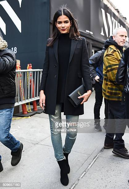 Model Cris Urena is seen outside the Desigual show wearing a black jacket black sweater and blue ripped jeans with a YSL black leather purse during...