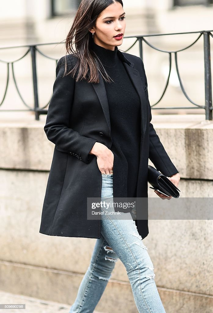 Model Cris Urena is seen outside the Desigual show wearing a black jacket black sweater and blue ripped jeans during New York Fashion Week Women's...
