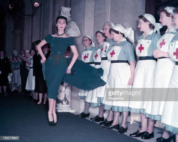 A model delights British Red Cross nurses in a creation by Christian Dior during the presentation of his Winter Collection at Blenheim Palace in the...