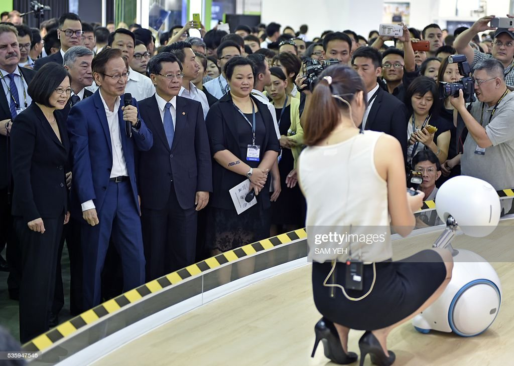 A model demonstrates a ASUS Zenbo robot as Taiwan President Tsai Ing-wen (L) looks on during the annual Computex computer exhibition on May 31, 2016. More then 5,000 booths from thirty countries take part in COMPUTEX Show between May 31 to June 4. / AFP / SAM YEH