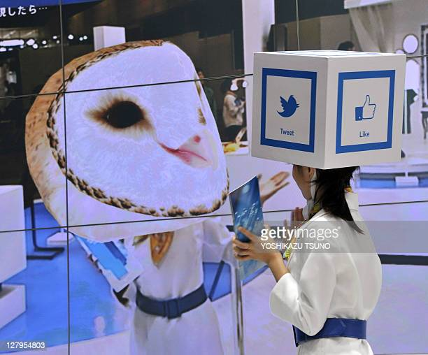 A model demonstrates augmented reality as her face is chaged to an owl on a large screen during a demonstration at US semiconductor giant Intel's...