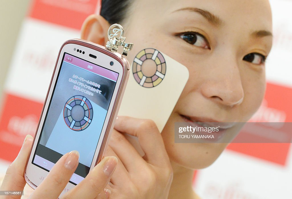 A model demonstrates how to take pictures of her face with a smart phone to chech her skin condition through a cloud computer system produced by Japan's computer maker Fujitsu during a press conference in Tokyo on November 29, 2021. Fujitsu started the new service using cloud computer technology for cosmetic makers, beauty treatment and healthcare service companies on November 29. AFP PHOTO/Toru YAMANAKA