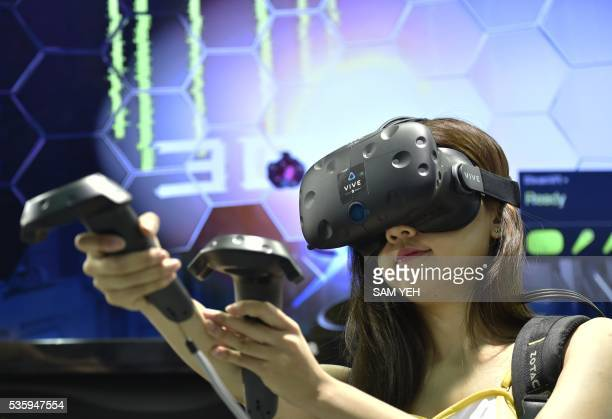 A model demonstrates the HTC Vive visual reality headset during the annual Computex computer exhibition in Taipei on May 31 2016 More then 5000...