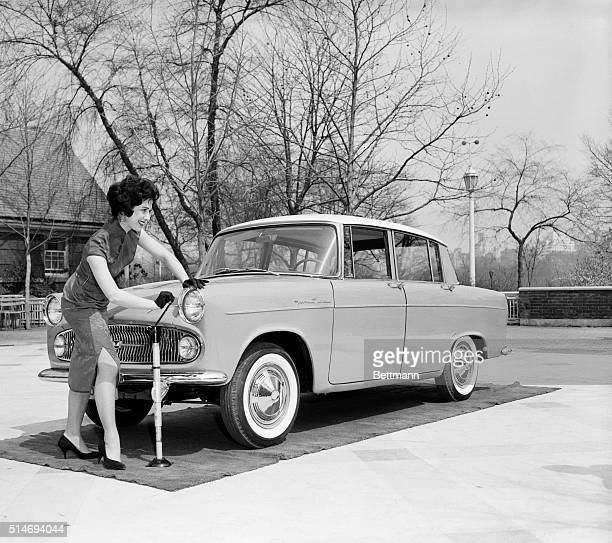 Model Diane Chiljan jacks up a Toyopet Tiara subcompact car from Japan during its unveiling in New York