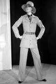 A model displays 08 February 1969 in Paris an Tcru gabardine trouserss suit with sleeveblouse large patchpockets military styled and strawhat for...