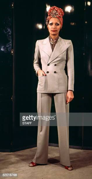 A model displays 15 February 1971 in Paris a doublebreasted beige gabardine trousers suit pointed flaps reaching the arm holes over a white dots...