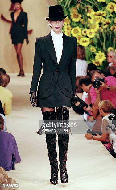 A model displays 20 July 1994 in Paris a black barathea smoking with short skirt white Roman crepe blouse and crocodile thigh boots gloves and hat...