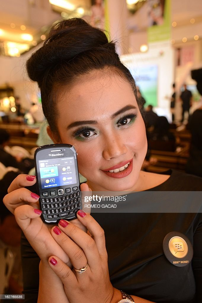 A model displays A Blackberry mobile phone with a Bank Permata program during a ceremony in Jakarta on February 26, 2013 as the two companies launched the world's first instant messaging banking service in Indonesia, capitalising on the nation's addiction to the smart phone that is losing popularity in other key markets. The Blackberry service features 'BBM Money' that allows account holders with Bank Permata -- partly owned by Standard Chartered Bank -- to make peer-to-peer money transfers and top up their phone credit by sending funds to service providers. AFP PHOTO / ROMEO GACAD