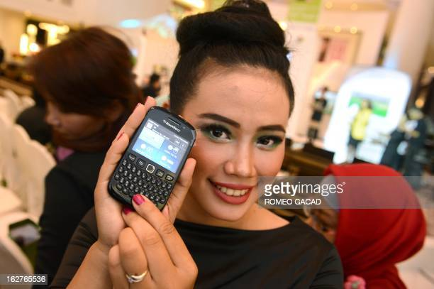 A model displays A Blackberry mobile phone with a Bank Permata program during a ceremony in Jakarta on February 26 2013 as the two companies launched...