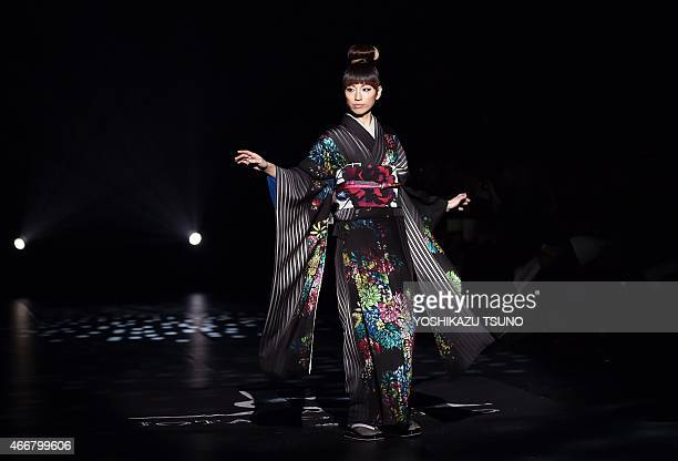 A model displays a creation by Japanese designer Jotaro Saito during his 201516 autumn/winter kimono collection in Tokyo on March 19 2015 as a part...