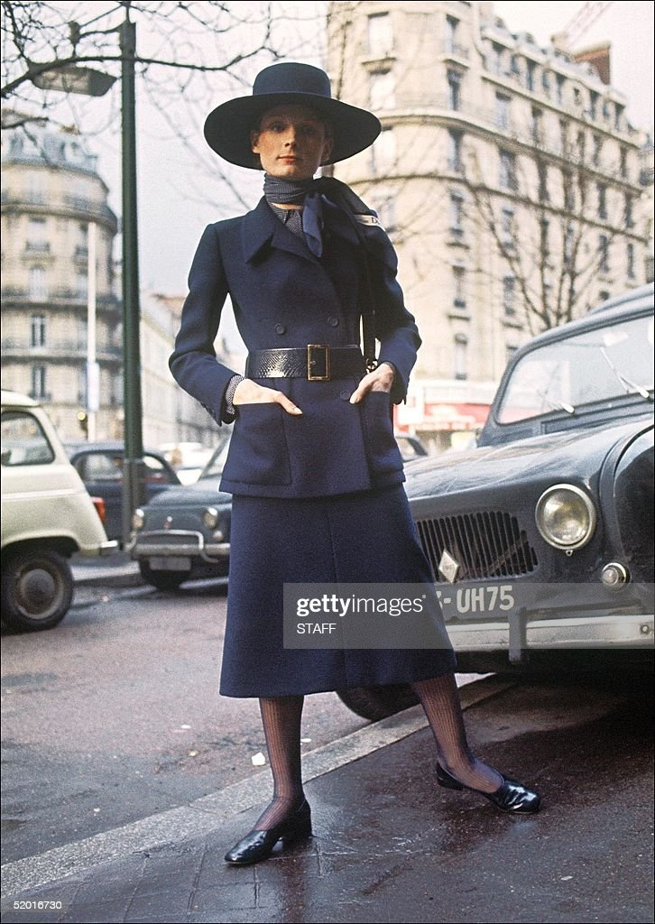 A model displays a long navy blue tailor suit, wide belted long jacket with two patch pockets, scarf and hat matched 04 February 1970 in Paris for Christian Dior 1970 Spring/Summer haute-couture collection.