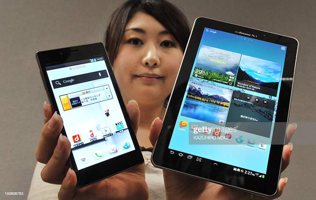 A model displays a new high-spec smartphone 'Optimus G L-01E' (L) and the world's largest organic EL display at 7.7 inches tablet 'GALAXY Tab 7.7 Plus SC-01E' (R) by Japanese mobile phone carrier NTT DoCoMo during a press preview in Tokyo on August 28, 2012. NTT DoCoMo unveiled three new smartphones and two new tablets, all compatible with the company's Xi LTE mobile service, for launch in or after September. AFP PHOTO / KAZUHIRO NOGI