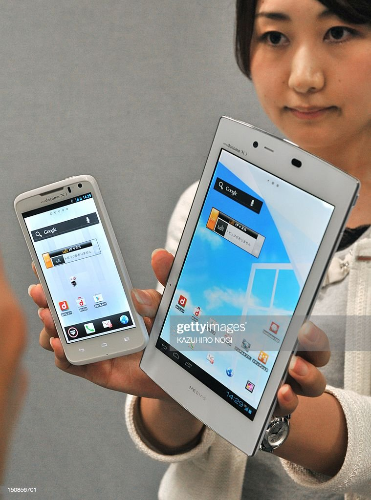 A model displays a new smartphone 'Ascend HW-01E' (L) and the world's lightest tablet with a 7-inch display weighing 249 grams 'MEDIAS TAB UL N08' (L) by Japanese mobile phone carrier NTT DoCoMo during a press preview in Tokyo on August 28, 2012. NTT DoCoMo unveiled three new smartphones and two new tablets, all compatible with the company's Xi LTE mobile service, for launch in or after September.