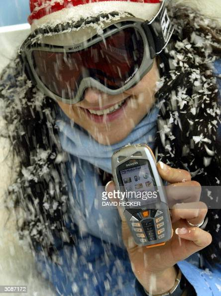 A model displays a Siemens M65 'Outdoor' mobile phone during a press preview at the CeBIT 2004 computer fair in Hanover 15 March 2004 The CeBIT 2004...