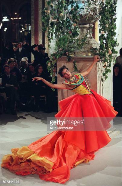 A model displays a sunset shaded silk tulle and organza bustier ball gown over trailing skirts and petticoats with a multicolor tiny pearl Maasai...