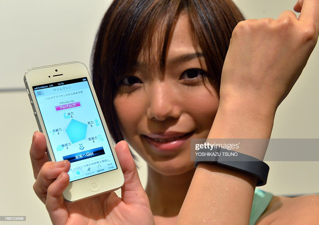A model displays a wristband device 'Fitbit Flex' and a smartphone as Japan's mobile operation giant Softbank announces the launch of the new health care service in Tokyo on May 7, 2013. The Fitbit Flex monitors data through a pedometer, calorie consumption and hours of sleep and transfers the information to a smartphone to maintain the user's health. Softbank is expecting to start the service from this summer. AFP PHOTO / Yoshikazu TSUNO