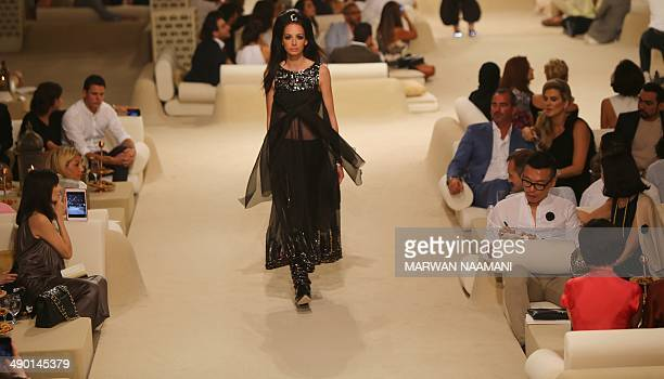 A model displays an outfit from the Chanel 2014/2015 Cruise collection at The Island in Dubai a man made island in the shape of a palm tree on May 13...