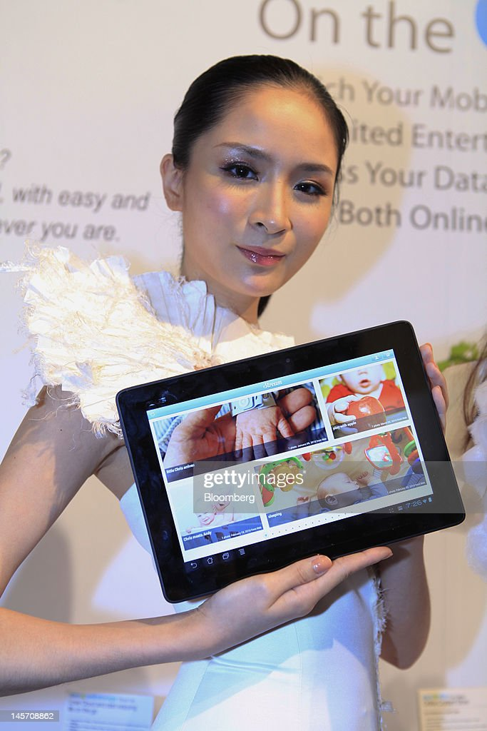 A model displays Asustek Computer Inc.'s ASUS FT300 at a news conference in Taipei, Taiwan, on Monday, June 4, 2012. Asustek today previewed a tablet using ARM Holdings Plc technology and running Microsoft Corp.'s Windows 8 operating system. Photographer: Ashley Pon/Bloomberg via Getty Images