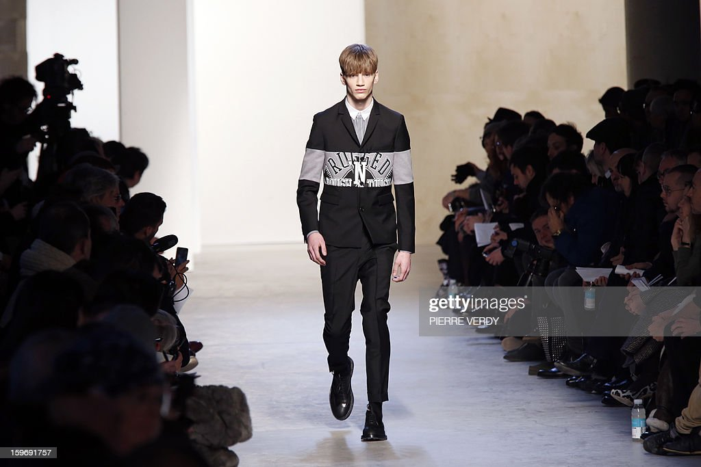A model displays creations by Belgian designer Kris Van Assche on January 18, 2013 during his men's fall-winter 2013-2014 fashion collection show during the fashion week in Paris. AFP PHOTO / PIERRE VERDY