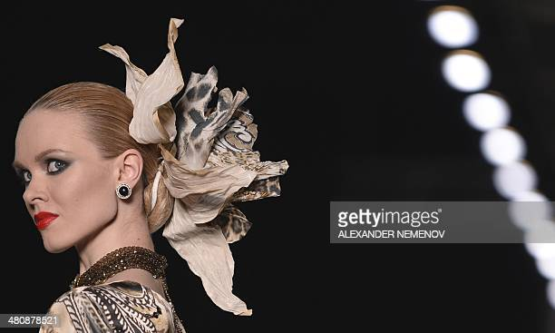 A model displays creations by Russian fashion designer Slava Zaitsev during a fashion show in Moscow on March 27 2014 AFP PHOTO / ALEXANDER NEMENOV