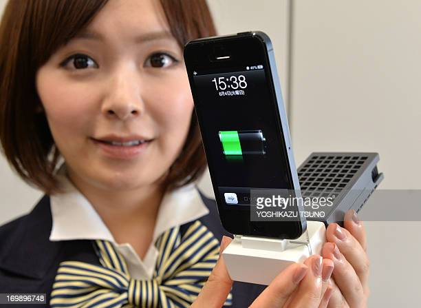 A model displays displays a solid fuel type cell 'Mobile aqua' charging the battery of a smartphone at a press preview in Tokyo on June 4 2013 The...