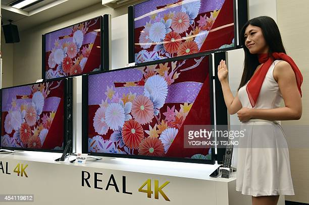 A model displays Japanese electric maker Mitsubishi Electric's new 4K television 'Real LS1' which has 65inch and 58inch sized LCD display in Tokyo on...