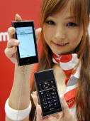 A model displays Japanese mobile communication giant NTT docomo's prototype mobile phone which enables it to separate its display and keyboard parts...