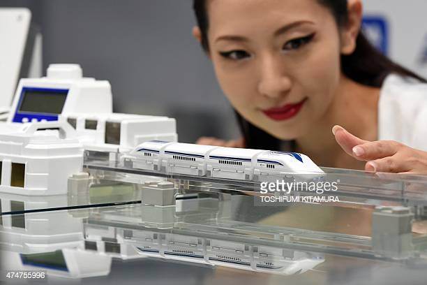 A model displays Japanese toy maker Takara Tomy's new maglev train toy 'LinearLiner' during a press preview in Tokyo on May 26 2015 The toy uses...