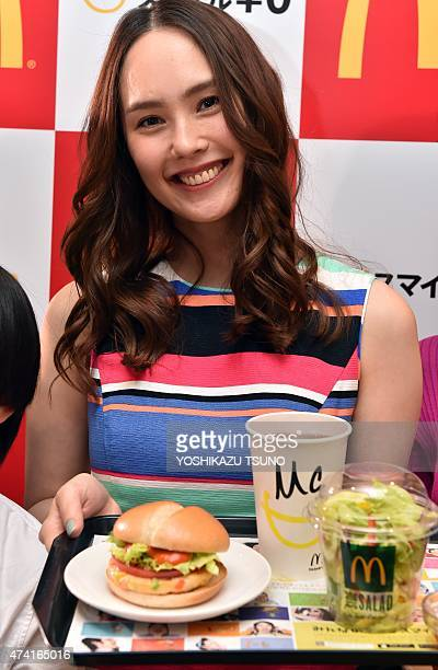 A model displays McDonald's Japan new menu 'Vegetable Chicken Burger' as the company president Sarah Casanova announces the new business strategy at...
