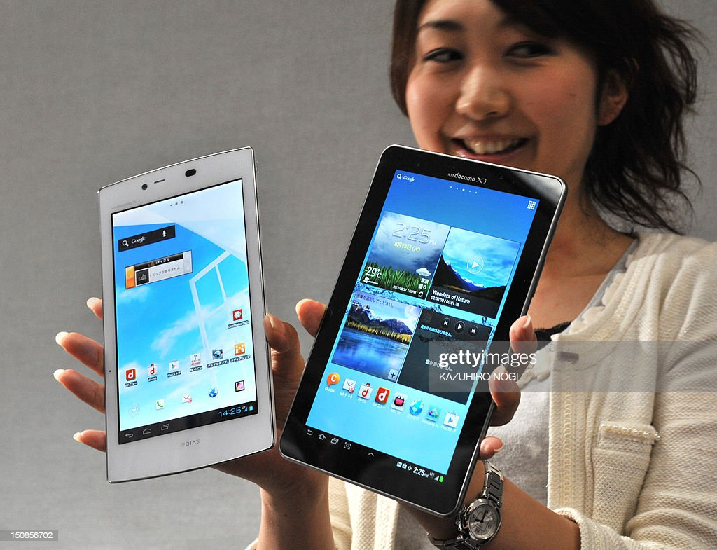 A model displays new tablets, the world's lightest tablet with a 7-inch display weighing 249 grams 'MEDIAS TAB UL N08' (L) and the world's largest organic EL display at 7.7 inches tablet 'GALAXY Tab 7.7 Plus SC-01E' (R) by Japanese mobile phone carrier NTT DoCoMo during a press preview in Tokyo on August 28, 2012. NTT DoCoMo unveiled three new smartphones and two new tablets, all compatible with the company's Xi LTE mobile service, for launch in or after September.