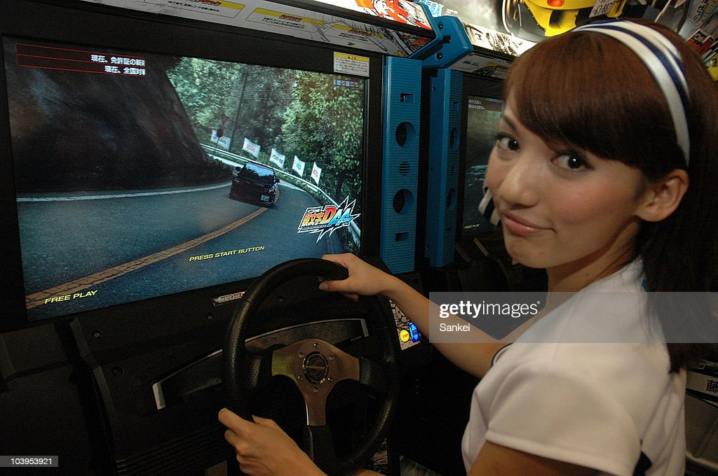 A model displays Sega's racing game 'Initial D Arcade Stage 6 Double Ace' during the 48th Amusement Machine Show at Makuhari Messe on September 9, 2010 in Chiba, Japan. The show, open until September 11, is for arcade video game machine industry, whose size of market has been shrinking year by year.