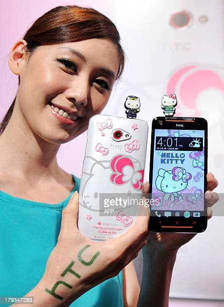 A model displays Taiwan electronics giant HTC's new smartphone 'HTC Butterfly S Hello Kitty' with accessories during a press conference in Taipei on...