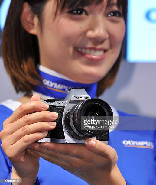 A model displays the new digital camera of Japanese camera maker Olympus 'OMD' which is classical design but mirrorless compact body at the annual...