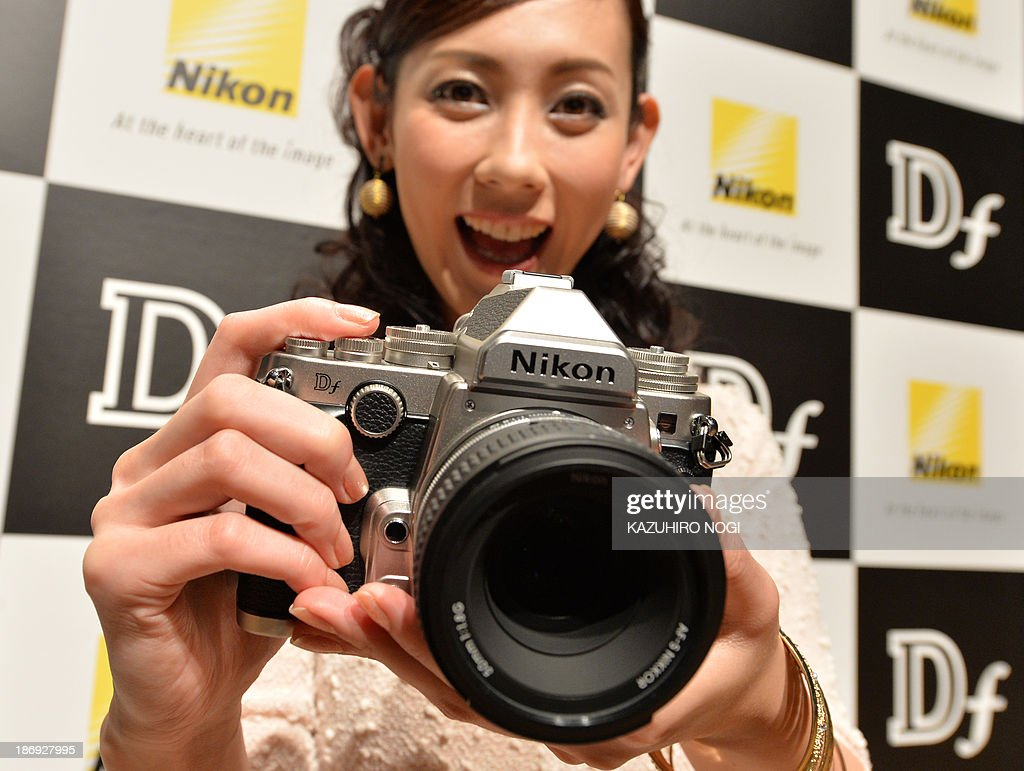 A model displays the new FX-format digital SLR camera 'Df' from Japanese camera maker Nikon during a press preview in Tokyo on November 5, 2013. Nikon will put the new camera, equipped with the same FX-format CMOS sensor, effective pixel count of 16.2-million pixels, and EXPEED 3 image-processing engine as the D4 flagship model on the domestic market on November 28.
