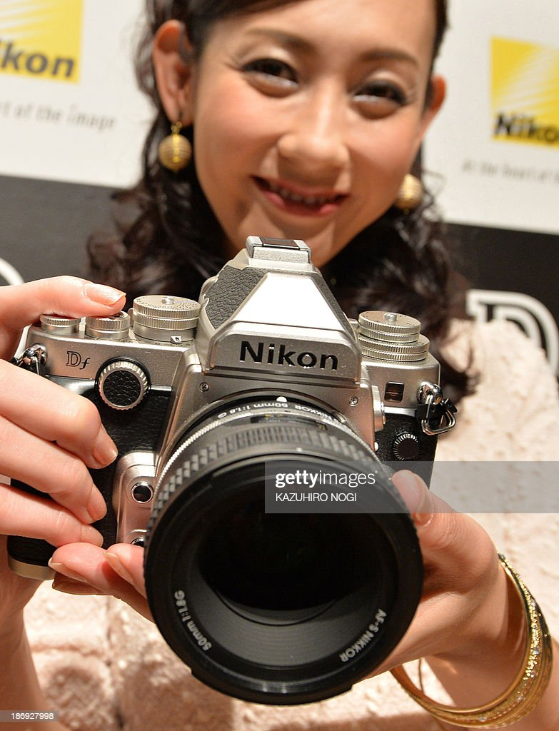 A model displays the new FX-format digital SLR camera 'Df' from Japanese camera maker Nikon during a press preview in Tokyo on November 5, 2013. Nikon will put the new camera, equipped with the same FX-format CMOS sensor, effective pixel count of 16.2-million pixels, and EXPEED 3 image-processing engine as the D4 flagship model on the domestic market on November 28. AFP PHOTO / KAZUHIRO NOGI