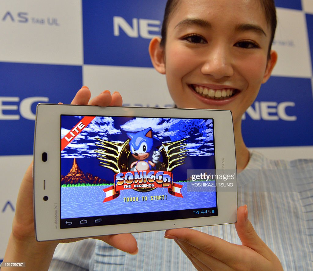 A model displays the new tablet device from Japanese electronics manufacturer NEC called 'Medias Tab N-08D' and its pre-installed Sega video game called Sonic at a preview in Tokyo on September 11, 2012. The new tablet, equipped with a seven-inch touch-screen display, weighs only 249g and will go on sale on September 20 through Japan's mobile communication company NTT DoCoMo. AFP PHOTO / Yoshikazu TSUNO