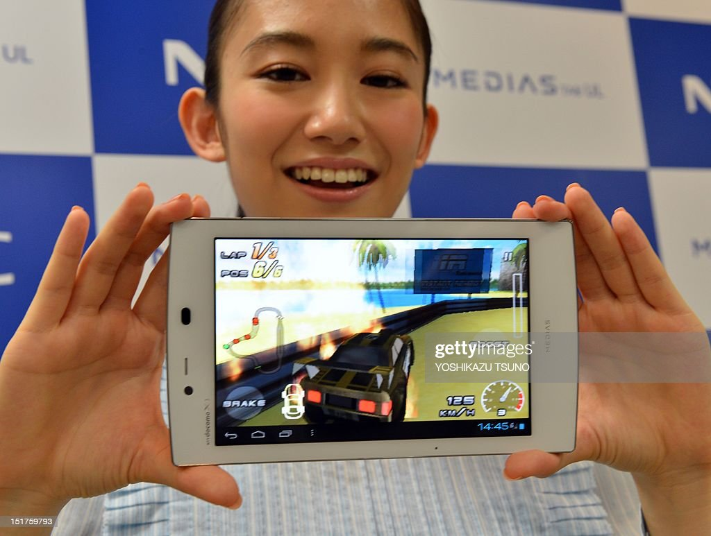 A model displays the new tablet device from Japanese electronics manufacturer NEC called 'Medias Tab N-08D' and its pre-installed video game called 'Racing Thunder2' at a preview in Tokyo on September 11, 2012. The new tablet, equipped with a seven-inch touch-screen display, weighs only 249g and will go on sale on September 20 through Japan's mobile communication company NTT DoCoMo. AFP PHOTO / Yoshikazu TSUNO