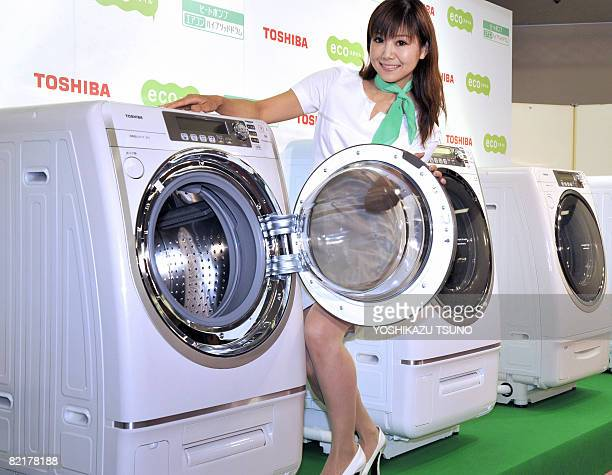 A model displays the new washing and drying machine of Japanese electronics giant Toshiba 'TW5000' which achieves low power consumption and...