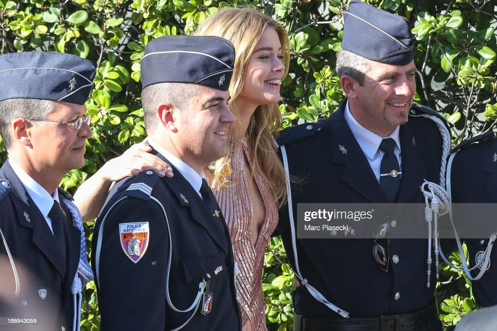 Model <a gi-track='captionPersonalityLinkClicked' href=/galleries/search?phrase=Doutzen+Kroes&family=editorial&specificpeople=859655 ng-click='$event.stopPropagation()'>Doutzen Kroes</a> poses with french policemen as she is seen leaving the 'Grand Hyatt Hotel Martinez Cannes' during the 66th annual Cannes Film Festival on May 17, 2013 in Cannes, France.