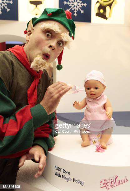 A model dressed as a Christmas elf plays with the 'Baby Born' with magic potty at the Toy Retailers Association's Dream Toys 2008 media preview St...
