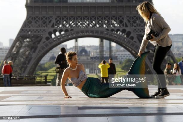 A model dressed as a mermaid prepares before posing in front of the Eiffel Tower during sunrise on May 22 2014 in Paris AFP PHOTO / LUDOVIC MARIN