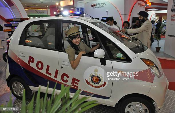 Model dressed as woman cop poses with Nano car specially designed for police at the India International Security Expo on September 26 2013 in New...