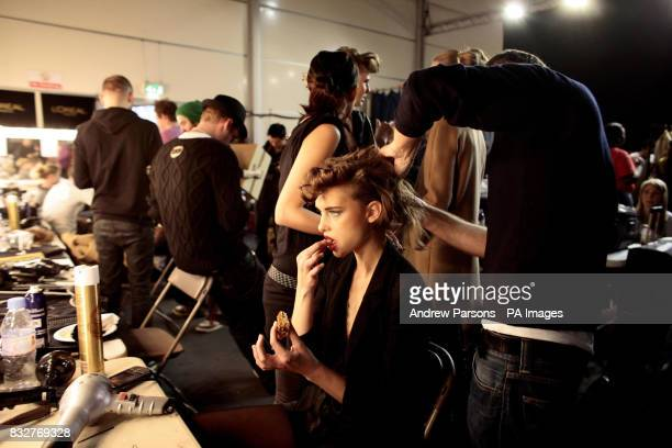 A model eating a sandwich backstage at the London Fashion Week Autumn/Winter 2007 in the Natural History Museum west London
