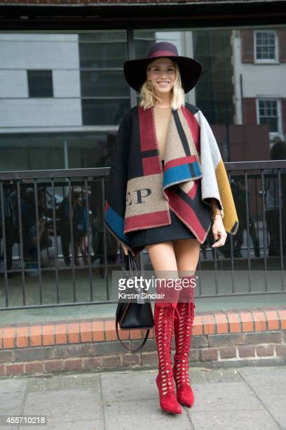 Model Elena Perminova is wearing a Burberry coat and Versace boots on day 3 of London Collections Women on September 14 2014 in London England