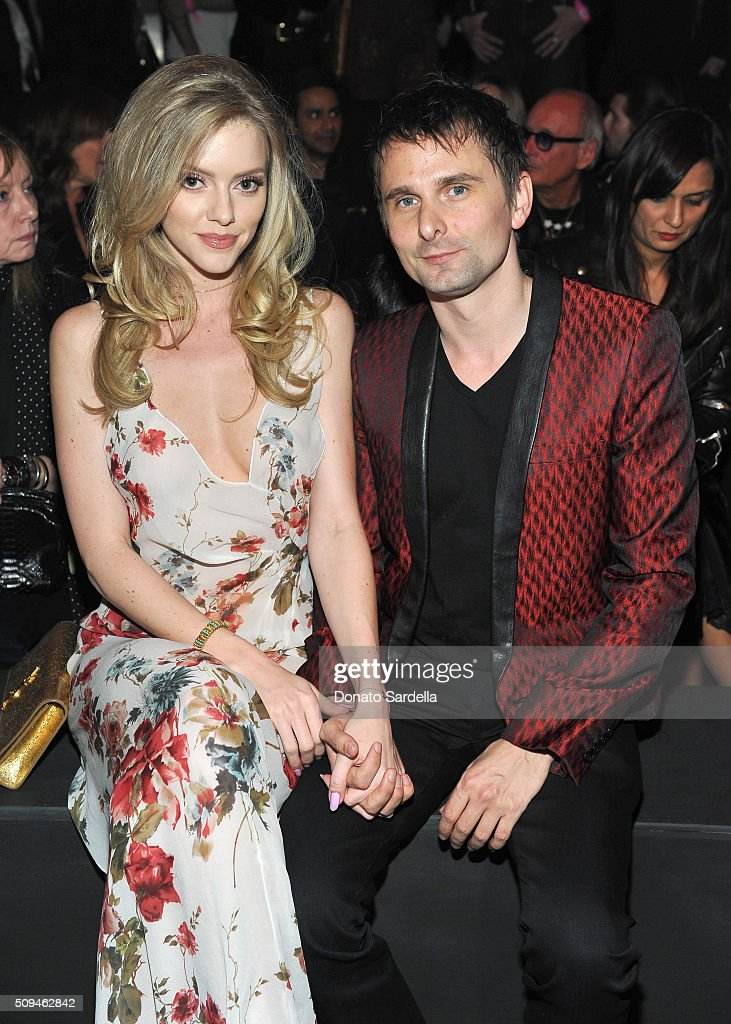 Model Elle Evans (L) and recording artist Matt Bellamy of Muse, in Saint Laurent by Hedi Slimane, attend Saint Laurent at the Palladium on February 10, 2016 in Los Angeles, California for the Saint Laurent Los Angeles show.