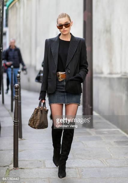 Model Elsa Hosk with braids wearing a blazer denim mini skirt overknees fishnet tights outside Balmain on March 2 2017 in Paris France