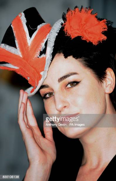 Model Erin O'Connor models a brightly coloured couture hat at the Victoria and Albert Museum in London