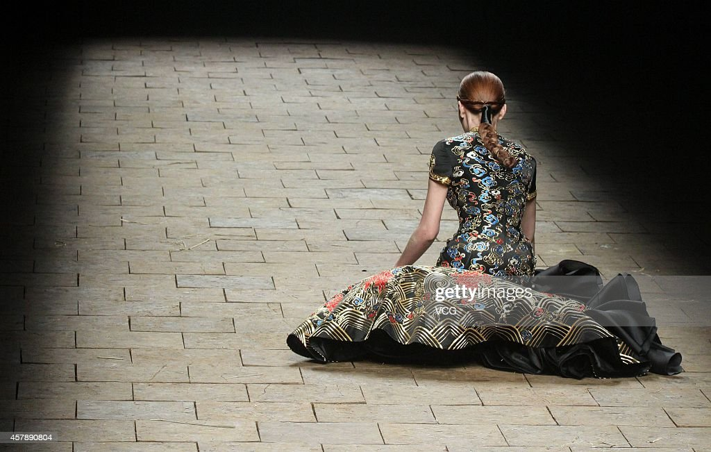 A model falls over on the runway at 2015 NETIGER Haute Couture Collection show during the first day of the MercedesBenz China Fashion Week...